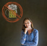 No beer alcohol woman smiling hand on chin on blackboard background. No beer alcohol alcoholic business woman, student or teacher smiling hand on chin on Royalty Free Stock Photo