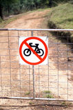 No Bicycles. No Bicycle sign attached to a gate across a dirt road stock photo