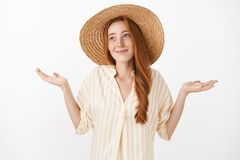 No big deal. Portrait of carefree optimistic charming kind female with ginger hair and freckles in cute straw hat and royalty free stock photo