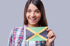 The are no boundaries for friendship. Happy young woman flag of Jamaica while standing against grey background Stock Photo