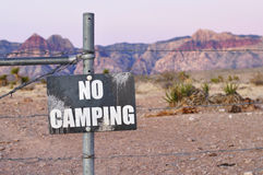 No camping. Sign posted on fence in desert royalty free stock photo