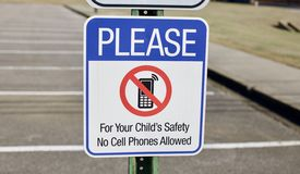 No Cell Phone Safety Sign. A sign warns that cell phone usage is banned in this area stock photography