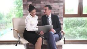 No centro de negócios no escritório para negociações um homem e uma mulher estão revendo documentos em uma tabuleta video estoque