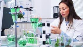 No centro de pesquisa da bioquímica o cientista fêmea está olhando amostras do teste da planta video estoque