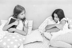 No chce dzielić jej książkę Siostry rywalizaci pojęcie Siostr powiązań zagadnienia Części książka z przyjacielem Dzieci wewnątrz fotografia royalty free