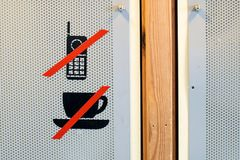 No coffee cup or drinks and mobile phone prohibition sign on the auditorium door. Are setting the rules in the interior Stock Images