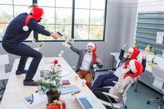 No corporaçõ do Natal no escritório, os empregados gracejam e jogam o dinheiro fotos de stock