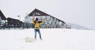 No dia de inverno duro com o homem do turista da neve que joga com um cão branco da montanha, ao lado de sua casa do bnb na parte video estoque