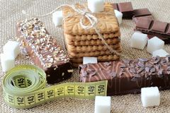 No diabetes and excess weight. Sweet shortbread biscuits tied with jute cord, pieces of sugar, dark chocolate and cakes covered wi stock photos