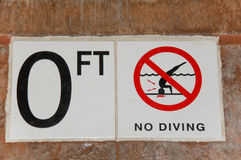 No Diving Sign for 0 Ft on the side of a pool with no diving icon. White sign on tile of the side of a pool with 0 ft and no diving with red circle and line Royalty Free Stock Photo