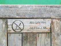 No diving and depth sign at pool. No diving warn sign and two meters depth at side of swimming pool Royalty Free Stock Photo