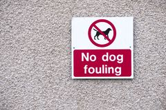 No dog fouling large clear sign on wall royalty free stock photo