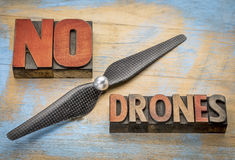 No drones sign or banner. Word abstract in vintage letterpress wood type blocks with a drone propeller stock photo