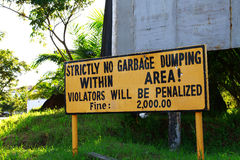 No dumping. A sign that reads NO DUMPING - VIOLATORS WILL BE FINED. Great for the going green environmental movement Royalty Free Stock Image