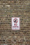 No dumping sign on a brick wall. No dumping sign on a brown brick wall Royalty Free Stock Photo