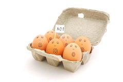 No eggs. A box with six brown eggs with scared facial expression and sign (no!). Image isolated on white studio background Royalty Free Stock Photography