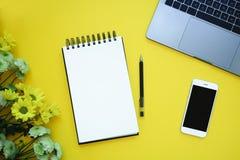 No en fondo amarillo con el teléfono, las flores y el ordenador portátil Copie el espacio imagen de archivo