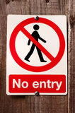 No entry sign. A no entry sign warning people not to go beyond the sign. The sign is a universal red colored round circle with a person inside. There is a royalty free stock photography