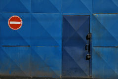 No entry sign by door. Blue door with no entry symbol posted nearby Stock Photos