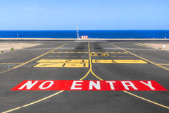 No entry sign at the runway of the airport with ocean in backgro Royalty Free Stock Image