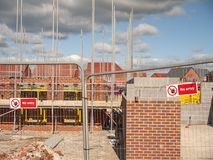 No entry warning sign on building site in Cheshire UK. New build houses behind security fence with No Entry warning sign on a new housing estate in Cheshire royalty free stock photos