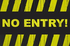 """No Entry!"" warning sign with yellow and black stripes painted over cracked wood. ""No Entry!"" warning sign with yellow and black stripes painted Royalty Free Stock Photo"