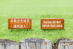 No entry wooden sign in English and Chinese placed on green gras Stock Images