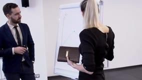 No escritório do olhar do colega na reunião uma mulher tira um gráfico a bordo vídeos de arquivo