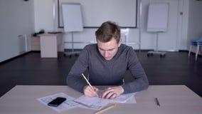 No escritório espaçoso o especialista usa um lápis para tirar uma disposição de papel video estoque