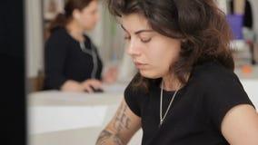 No escritório há uma mulher com tatuagens e pirsong no computador filme