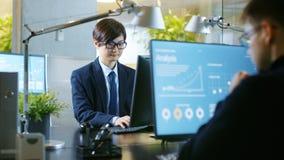 No escritório o homem de negócios asiático do leste trabalha em um Desktop pessoal imagem de stock royalty free