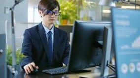No escritório o homem de negócios asiático do leste trabalha em um Desktop pessoal imagem de stock