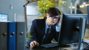 No escritório o homem de negócios desesperado trabalha em um Desktop pessoal imagens de stock