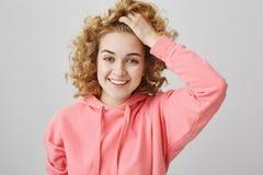 No esperaba verle Retrato de la hembra rizado-cabelluda encantadora en la sudadera con capucha rosada que lleva a cabo la tracció Imagenes de archivo
