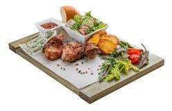 No espeto da carne de porco com salada, as batatas e molho vegetais fotografia de stock