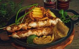 No espeto da galinha em espetos de madeira com os vegetais rústicos imagem de stock