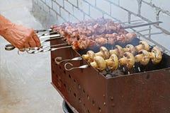 No espeto e cogumelos masculinos da carne do churrasco da mão em um soldador Fotografia de Stock