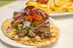No espeto grego no pão árabe com cebolas, tomates Culinária grega tradicional fotografia de stock royalty free