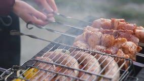 No espeto grelhado no espeto do metal O cozinheiro chefe entrega o cozimento do assado roasted da carne com lotes do fumo Costele filme