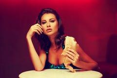 No espeto lindo comer da mulher no clube noturno fotos de stock