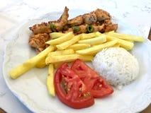 No espeto turco da galinha com arroz Pilav ou batatas e tomate/Sis Kebap do pilau Imagens de Stock