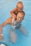 No está diversión a ser el padre de un pequeño niño en el par del agua Foto de archivo