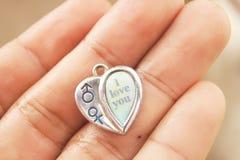 No estilo do pendente do coração da posse das mãos tenha o vocabulário inglês EU TE AMO imagem de stock