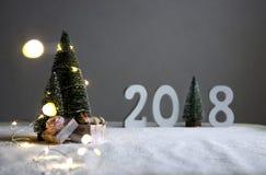 No fieldthe um cão está dormindo em presentes e na distância estão figuras 2018 onde no papel de uma árvore de Natal com luzes Imagem de Stock
