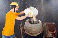O trabalhador está limpando o misturador de cimento quando a chuva grande cair Fotos de Stock Royalty Free