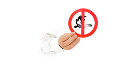 No fire sign, hand. Hand of man breaking through a paper wall and showing no fire in area warning sign. Copy space. Studio shot. White background Stock Photos