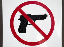No Firearms. A scratched up no gun sign mounted on a door Royalty Free Stock Images