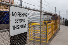No fishing beyond this point sign on mesh fence Stock Images