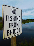 No Fishing From Bridge Sign Infront of a Beautiful River Royalty Free Stock Photo