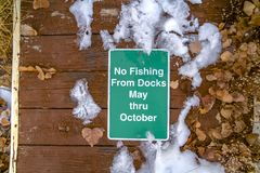 No Fishing From Docks May Thru October sign. Close up view of a  posted on the wooden dock of a lake. Icy snow and dry leaves can be seen around the sign royalty free stock images